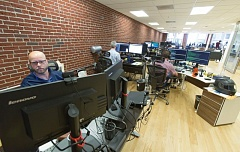 Photo Credit: TRIBUNE PHOTO: JON HOUSE - Brian Hollet works in the open floor of Rentrak's downtown office.