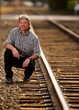 Photo Credit: TIMES PHOTO: JAIME VALDEZ - Aloha author D.C. Jesse Burkhardt, seen crouching along the tracks behind Southwest Broadway Street, has always held the mystique of railroads and trains close to his heart.