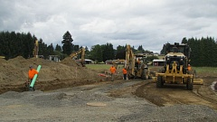 Photo Credit: COURTNEY VAUGHN - A construction crew works on a D.R. Horton housing development site at the Dutch Canyon Estates in Scappoose. The city voted Monday to lower System Development Charges related to water meter installations.