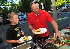 Photo Credit: REVIEW PHOTO: VERN UYETAKE - Fifth-grader Levi Brown and his dad, Jerry, dish up dinner at the Lakeridge Junior High BBQ on Friday.