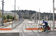 Photo Credit: TRIBUNE PHOTO JONATHAN HOUSE - A cyclist passes by the new transit center under construction on the east side of the Tilikum Crossing in Southeast Portland where the Division-Powell line could connect.