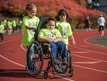 Photo Credit: SPOKESMAN PHOTO: JOSH KULLA - Alina Boyd and her friend Trinity, both fourth-graders taught by Traci Hallock-Gross, show that you don't have to be limited by disability to help the cause by pushing classmate Issac Dreyling during the annual Boeckman Creek Fun Run last Friday.