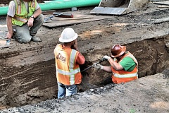 Photo Credit: DAVID F. ASHTON - In the trench, workers investigate a gas line, broken while digging up S.E. 32nd Avenue to replace Eastmoreland sewer pipes.