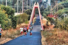 Photo Credit: DAVID F. ASHTON - At sunset, Hood to Coast runners jog across the Springwater Trails McLoughlin Boulevard Pedestrian Bridge, making their long, long way to Seaside at the coast.