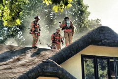 Photo Credit: DAVID F. ASHTON - Firefighters wait for orders to cut another hole for vertical ventilation, on the stately Garthwick home, just north of the Waverley Golf Club.