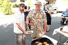 Photo Credit: DAVID F. ASHTON - Former Reed Neighborhood Association Chair Gabe Headrick receives a sizzling cheeseburger from chef Mark Gossage at this years neighborhood picnic.
