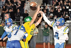 Photo Credit: SETH GORDON - Newberg quarterback Kasey Fish unleashes a throw in the face of pressure from a West Linn defender during the Tigers' 48-14 road loss Friday.