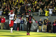 Photo Credit: TRIBUNE PHOTO: JAIME VALDEZ - Oregon's Byron Marshall leaps on receiver Keanon Lowe after Lowe's touchdown catch against Arizona.