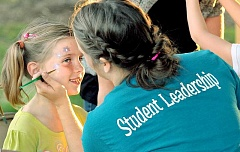 Photo Credit: SETH GORDON - Fun for all students - Senior Katelyn Reimer paints a young C.S. Lewis Academy student at the school's annual carnival on Friday.