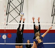 Photo Credit: JEFF WILSON/THE PIONEER - Kiana Adams, left, and Taylor Sjolund, right, go up to make a block during last week's volleyball match against Crook County. The Cowgirls would sweep Madras in three sets.