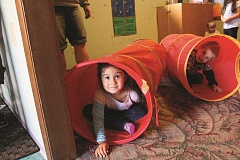 Photo Credit: TYLER FRANCKE | WOODBURN INDEPENDENT - Little Lambs Preschool students Izabelle Mendoza Ebata and Bradley Donavant peer out of play tunnels.
