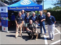 Photo Credit: SUBMITTED PHOTO - Tigard Police K-9 Baxter poses for a photo with his handler and members of the Tigard Breakfast Rotary who are working to raise money to purchase a second police dog for the department.