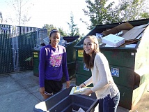 Photo Credit: SUBMITTED PHOTO - Westside Christian High School students Chloe Brown and Danielle Simmons unload garbage into a Dumpster as part of Get Out! Serve Day, a day-long community service project across Tigard and Beaverton.