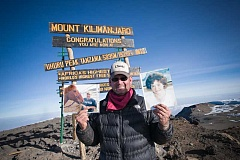 Photo Credit: CONTRIBUTED PHOTO - Jason Wood poses at the summit of Kilimanjaro with pictures of his mother and brother.