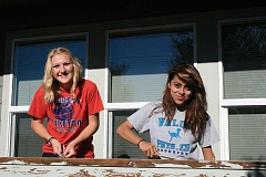 Photo Credit: SUBMITTED PHOTO BY LOUJEAN FOBERT - Lauren Stokley (left), of Immanuel Lutheran Church in Woodburn and a student at Kennedy High School in Mt. Angel, and Adriana Isidoro (right) a National Honor Society student at WeBBS in Woodburn, scrape old paint from a porch railing in preparation for new paint.