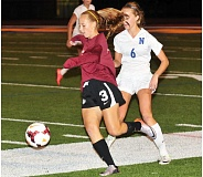 Photo Credit: PAMPLIN MEDIA GROUP: SETH GORDON - WOLF ON THE RUN -- Tualatin sophomore Sara Elam (left) controls the ball in front of Newberg's Maddie Whalen in last week's match.