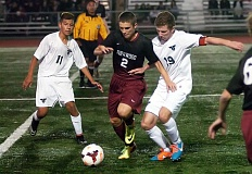 Photo Credit: DAN BROOD - ON THE PITCH -- Sherwood junior Benjamin LaFave (2) battles Tigard junior Brandon Pliego (11) and senior Clint Raye (19) for the ball in Tuesday's match.