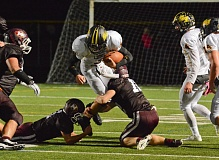 Photo Credit: JOHN WILLIAM HOWARD - St. Helens junior Bryce Bumgardner gets tripped up midway through the second quarter of the Lions' 25-21 loss to Milwaukie on Friday night.