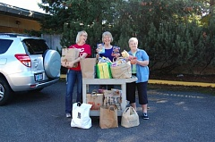Photo Credit: SUBMITTED PHOTO - Left to right, Michelle Baker, student life and leadership advisor and head of CCCs food bank, and Darby Walker and Dolores Smith, co-presidents of Clackamas District Garden Club, unpack donated items to stock the shelves at the food bank.