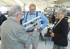 Photo Credit: PHOTO BY JIM DEMERS - Leo Demers Jr., left, examines the Wright Flyer awarded to his late father, Leo 'Ace' Demers Sr. Demers was accompanied by Bill Kullman, of Culver, and his wife, Mary Lou. Ace Demers' younger son, Jim, and his wife, Shirley, also attended the event honoring the aviation pioneer.