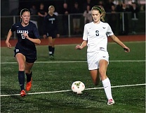 Photo Credit: DAN BROOD - ON THE TURF -- Tigard senior Sarah Schaffer (right) moves the ball up field ahead of Lake Oswego sophomore Ellie Moreland in last week's match.