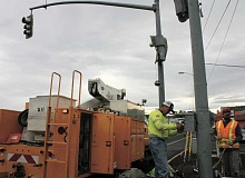 Photo Credit: JASON CHANEY - ODOT employees work to repair the damaged traffic signal at North Main Street and Lamonta Road on Wednesday afternoon.