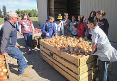 Photo Credit: GAZETTE PHOTO: BARBARA SHERMAN - Corey Dickman (left), who is the fourth generation to operate Dickman Farms, answers questions from Laurel Ridge students about how onions are harvested and stored.