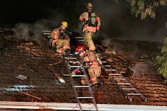 Photo Credit: DAVID F. ASHTON - On the roof of the burning home on S.E. Schiller Street, firefighters check holes they cut, to make sure the vertical ventilation is allowing superheated gasses to escape.