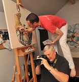 Photo Credit: STAFF PHOTOS: VERN UYETAKE - Painter Paul X. Rutz works on a portrait of West Linn veteran Lance Gregner. Gregner wanted his portrait to represent his interest in photography.