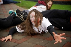 Photo Credit: POST PHOTO: TROY WAYRYNEN - Sandy High School student Jenn Burns, 18, made up as a zombie, reaches for runners in the Sandy High School Zombie Run and Walk to help raise money for the senior high school party.