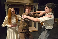 Photo Credit: TIDINGS PHOTO: VERN UYETAKE - A love triangle fuels the action of Oklahoma! with two men vying for the attention of Laurey, left, played by Amber Mitchell. In this scene, Curley, played by Soren Carr, grapples with Jud Fry, played by Dane Shroy.