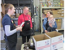 Photo Credit: BARBARA SHERMAN - King City Grocery Outlet employee Nicole Wulf (left) chats with store co-owner Tony Slater and Mission Mahalo co-founder Jennifer Lamaye, holding son Jordan, before they start packing boxes for troops stationed in Afghanistan.