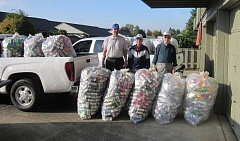 Photo Credit: BARBARA SHERMAN - Standing next to 17 full bags of cans collected over one month and stored at the King City Lions Club's garage are Ernie Karlson (left), Bill Gerkin and Ron Baker; the Lions previously collected 34 bags of cans over a two-month period since the fundraiser began.