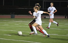 Photo Credit: TIMES PHOTO: MATT SINGLEDECKER - Jesuit senior forward Maddie Kincaid clips a shot past a North Medford defender in the first half of the Crusaders 1-0 loss in the second round of the 6A playoffs.