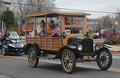 Photo Credit: HOLLY M. GILL - Veteran Bob Filomeo gets a ride in Jim Carroll's 1922 Model T Depot Hatch in the 2013 Veterans Day Parade. This year's parade takes off at 2 p.m. Tuesday, Nov. 11, down 10th Street and around Sahalee Park.