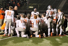 Photo Credit: JIM BESEDA/MOLALLA PIONEER - Molalla coach Kaleb Mitchell huddles with his team after Friday's 41-6 Class 4A playoff loss to Scappoose at Lincoln High School.