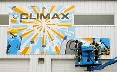 Photo Credit: GARY ALLEN - A splash of color - A pair of workers begin installation of a 3,000-square-foot mural Saturday on the southwestern wall of Climax Portable Machine and Welding Systems.