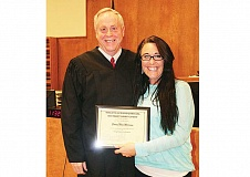 Photo Credit: HOLLY M. GILL - Emmy Morrison, right, proudly displays the certificate for graduating from Drug Court, presented by Circuit Court Judge Dan Ahern.