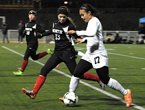 Photo Credit: PAMPLIN MEDIA: DAVID BALL - Tualatins Corinne Togiai, 17, races down the sideline against North Medford defender Meghan Cowan during the second half Saturday. Togiai netted both of the games goals within a five-minute stretch.
