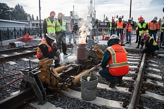 Photo Credit: TRIBUNE PHOTO BY VIRGINIA WERNER - Smoke and flames rise from the therite-fueled heating pot as molten metal makes the last weld on the new MAX line in Milwaukie.