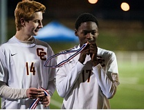 Central Catholic midfielder Peter del Mar (right) kisses his state championship medal as Rams forward Nick Evans watches, after CC's title game victory over Grant 3-0 at Hillsboro Stadium on Nov. 15.