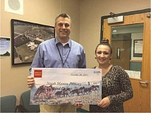 Photo Credit: SUBMITTED - Maricela Beach (right), branch manager of Wells Fargo in the west Woodburn location, presents a $1,000 check to Andy Kronser, vice principal of operations at North Marion Primary School. The grant money will go toward a fund to buy a reader board.