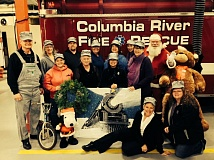 Photo Credit: COURTESY OF JAY TAPPAN - Organizers of the annual Merchant's Toy & Joy Benefit Auction in front of a Columbia River Fire & Rescue vehicle, from left to right: Jay Tappan, Lynne Tappan, Linda McDougle, Mike Dunning, Pam Hemstock, Jo Ann Turvey, Luanne Kreutzer, Monica Cade, Keirney Glenn-Barham, Linda Glenn-Barham and Merle Pence dressed as Santa Claus, with Debbie Ritthaler and Michele Hicks seated.
