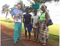 Photo Credit: COURTESY OF JOE YOUNG - Dr. Joe Young, who has a dental practice in King City, stands with a trio of Liberian women while holding a copy of the Regal Courier.