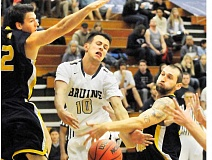Photo Credit: SETH GORDON - Battered - Johnathan Doutt gets roughed up on his way through the lane during George Fox's 81-65 home loss to Northwest University Saturday night at Miller Gym.