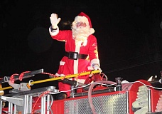 Photo Credit: HOLLY M. GILL - Santa waves from atop a fire truck in last year's Christmas Lights Parade.