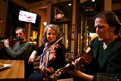 Photo Credit: TIMES PHOTO: JAIME VALDEZ - Brongaene Griffin, middle, plays the fiddle with Conor O'Bryan, left, and Bob Soper at Paddy's Bar & Grill.