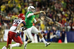 Photo Credit: TRIBUNE PHOTO: JAIME VALDEZ - Oregon's Marcus Mariota beats the Arizona rush and fires a pass during the Pac-12 championship game last week.