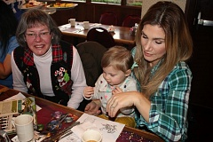 Photo Credit: OUTLOOK PHOTO: ANNE ENDICOTT - Gloria Weitzel, left, visits with Brittany Clark and her daughter Avery, 18 months, at a neighborhood holiday breakfast held Saturday, Dec. 6, at Heidis of Gresham.