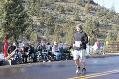Photo Credit: JEFF WILSON/THE PIONEER - Andy Winkleblack, of Bend, smiles as he passes in front of the Jefferson County Library Band while emerging from Willow Creek Canyon during Saturday's Canyon Rumble Frozen Half Marathon run. Warmer weather brought out more than 90 participants for this year's run. The band, which was situated just east of the railroad trestle on C Street, played Christmas tunes as the runners made their way up out of the canyon and into the city.